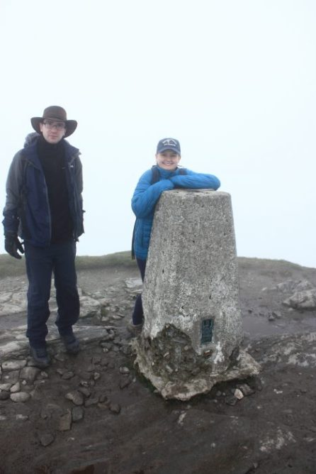 Simon and Eleanor pose by the Munro summit marker. © Angus Lothian